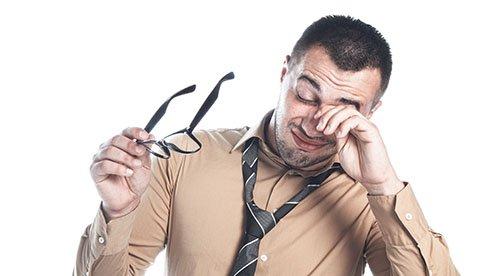 A Man Rubbing his Eyes